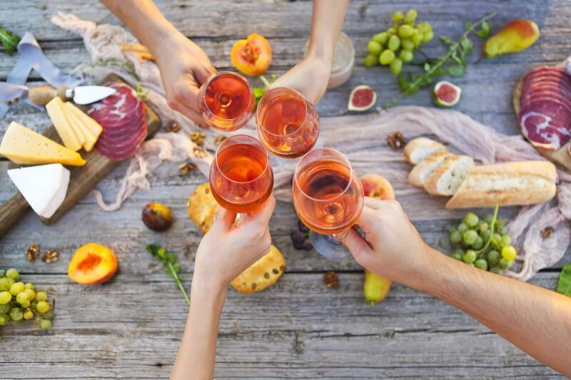 People toasting with rosé over a picnic table with food