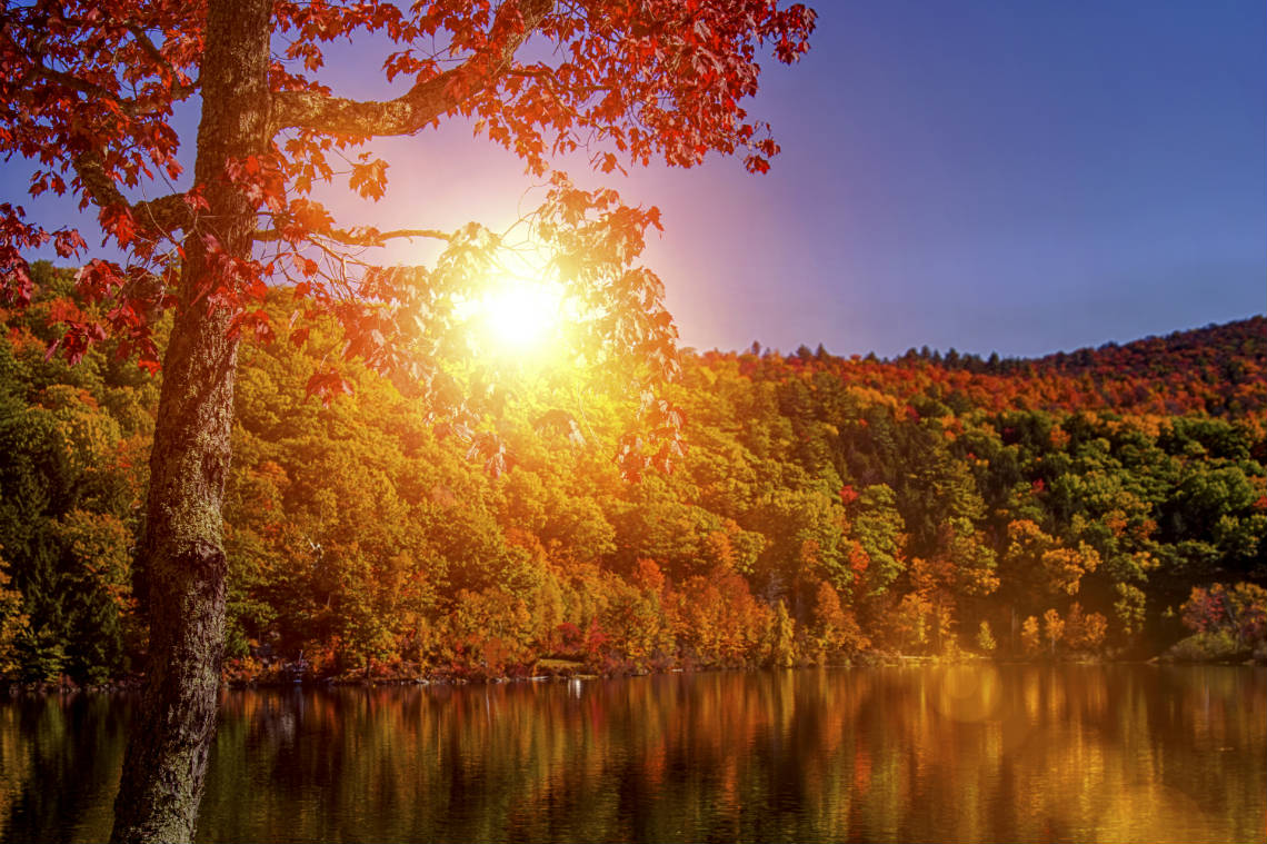 sun shining over lake in the fall in NH